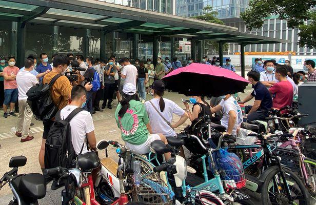 15일 중국 광둥성 선전에 있는 대형 민간 부동산 개발업체 헝다(恒大·에버그란데) 그룹 본사 앞에 보안요원들이 배치된 가운데 투자자들이 몰려들어 돈을 돌려달라고 요구하고 있다.